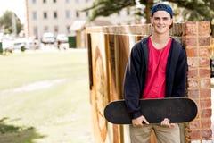 Adolescent avec la planche à roulettes se tenant dehors Photo libre de droits
