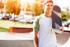 Adolescent avec la planche à roulettes se tenant dehors Image libre de droits