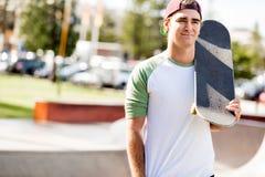 Adolescent avec la planche à roulettes se tenant dehors Images stock