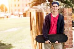 Adolescent avec la planche à roulettes se tenant dehors Photographie stock