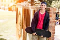 Adolescent avec la planche à roulettes se tenant dehors Image stock