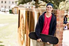 Adolescent avec la planche à roulettes se tenant dehors Photos libres de droits