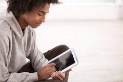 Adolescent avec le comprimé numérique. images stock