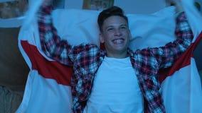 Adolescent avec le match de observation de drapeau anglais à la maison, soutenant l'équipe nationale banque de vidéos