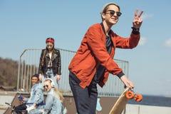 Adolescent avec le patin en parc de planche à roulettes avec des amis derrière Images stock