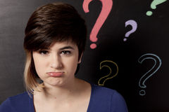 Adolescent and blackboard. With question marks royalty free stock photo
