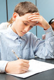 Adolescent Boy in Class. Boy taking test in class. Real person in real-life classroom situation stock photos