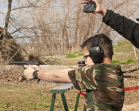 Adolescent boy shooting pistol with brass flying Royalty Free Stock Photography