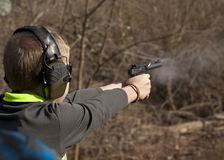 Adolescent Boy shooting pistol with smoke and brass flying Royalty Free Stock Photo