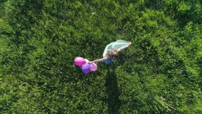 Adolescent with bright hair is spinning with balloons on background of green lawn on sunny day, aerial view. Adolescent with bright hair is spinning with stock footage