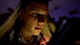 Adolescent causant ou jouant sur le smartphone se trouvant sous la couverture, d?pendance d'instrument image stock
