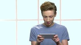 Adolescent concentré jouant le jeu sur le smartphone banque de vidéos