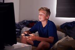 Adolescent dépendant au jeu visuel à la maison image stock