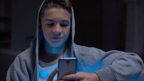 Adolescent dépendant d'instrument mettant en rouleau le contenu adulte sur le smartphone, perdant le temps banque de vidéos