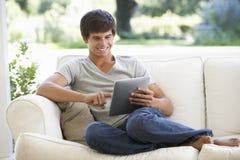 Adolescent détendant sur la Tablette de Sofa At Home Using Digital photographie stock libre de droits