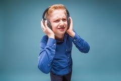 Adolescent dans des écouteurs avec un visage aigre écoutant la musique photos stock