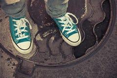 Adolescent dans des espadrilles Pieds dans des chaussures en caoutchouc, style ancien Photo stock