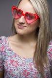 Adolescent dans des lunettes de soleil de forme de coeur Images stock