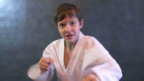 Adolescent dans l'ondulation de mains de combat de karaté de kimono clips vidéos