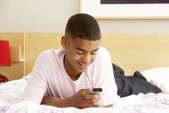 Adolescent dans la chambre à coucher avec le téléphone portable Photo stock