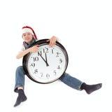 Adolescent dans le capuchon du père noël et de la grande horloge Photo stock