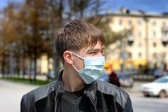 Adolescent dans le masque de grippe photo stock