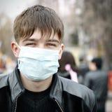 Adolescent dans le masque de grippe photographie stock