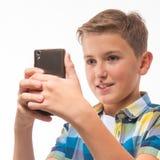 Adolescent dans une chemise de plaid avec un téléphone dans sa main Photos stock