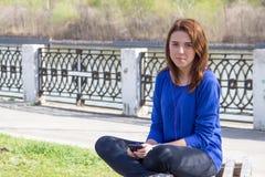 Adolescent de fille avec le téléphone écoutant la musique sur des écouteurs image stock