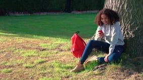 Adolescent de fille d'afro-américain s'asseyant par un arbre avec un sac à dos rouge et à l'aide d'un téléphone portable pour le  clips vidéos