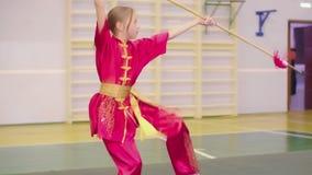 Adolescent de fille dans le yifu pour le chi de tai pour des arts martiaux formant des exercices de wushu banque de vidéos