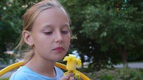 Adolescent de fille de portrait mangeant la crème glacée dans la fin de parc d'été  banque de vidéos