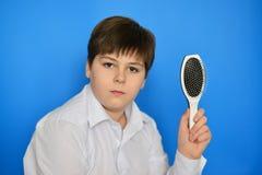 Adolescent de garçon avec le peigne dans sa main Images stock