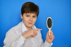Adolescent de garçon avec le peigne dans sa main Photos stock