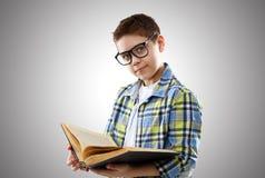 Adolescent de garçon d'enfant avec les verres et le livre Photos stock