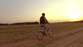 Adolescent de garçon montant une bicyclette L'adolescent de garçon montant une bicyclette va à la nature le long du mouvement vis Photo libre de droits