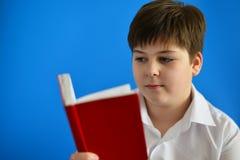 Adolescent de garçon regardant dans le planificateur de jour Images stock
