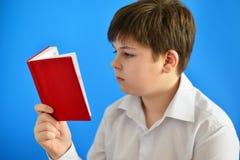 Adolescent de garçon regardant dans le planificateur de jour Photographie stock libre de droits