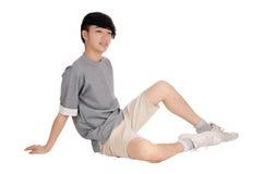 Adolescent de l'Asie s'asseyant sur le plancher Photos stock