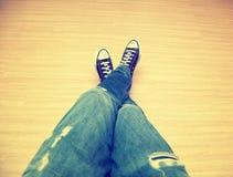 Adolescent de pied dans les jeans et des espadrilles classiques Image libre de droits