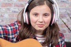 Adolescent de sourire avec des écouteurs, jouant la guitare Images stock
