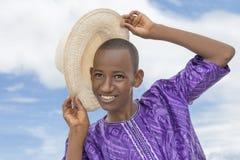 Adolescent de sourire tenant un chapeau de paille de chapeau en paille photographie stock libre de droits