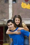 Adolescent donnant le tour de ferroutage d'amie Photographie stock