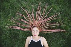 Adolescent dormant avec les tresses roses sur le parc Images stock