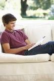 Adolescent détendant sur Sofa At Home Reading Book Images stock