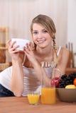 Adolescent eating breakfast. Teenage girl enjoying eating breakfast Stock Photography