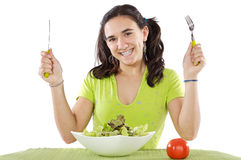 Adolescent eating a salad. A over white background royalty free stock image