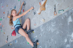 Adolescent escaladant un mur de roche Images libres de droits