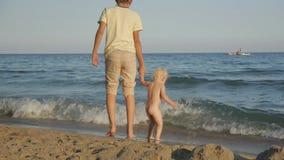 Adolescent et enfant ayant l'amusement sur la plage Deux années de bébé blond se tenant genou-profond dans l'eau et l'éclaboussem clips vidéos