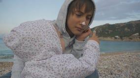 Adolescent et enfant ayant l'amusement sur la plage Plan rapproché de deux années de bébé à capuchon enduisant son nez de l'adole clips vidéos